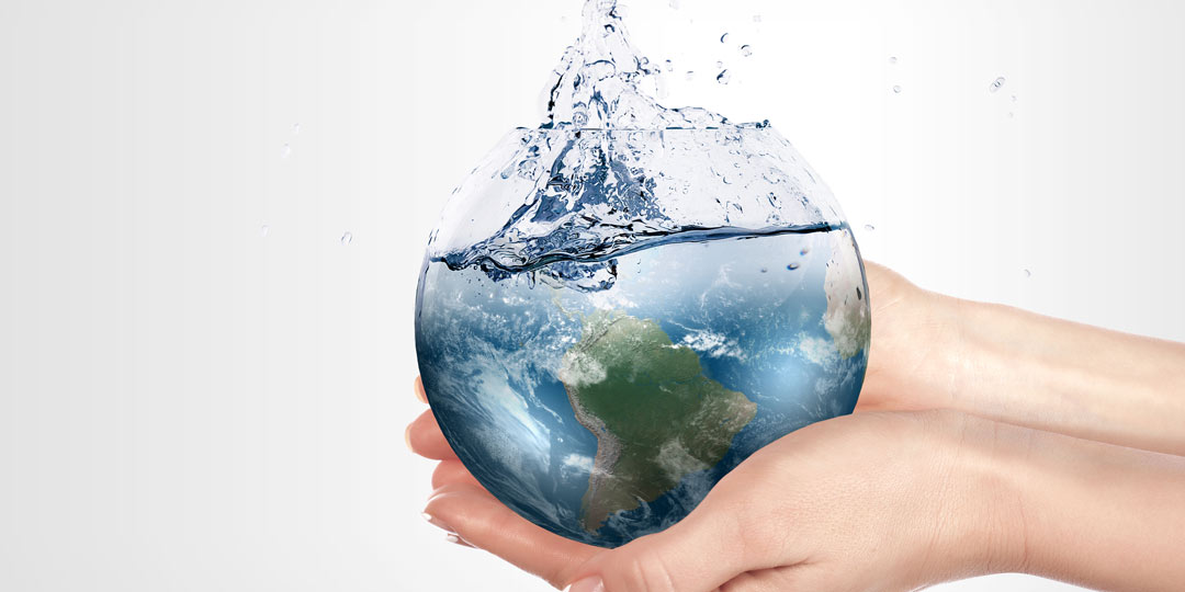 Hands holding a round glass full of water in the shape of the earth