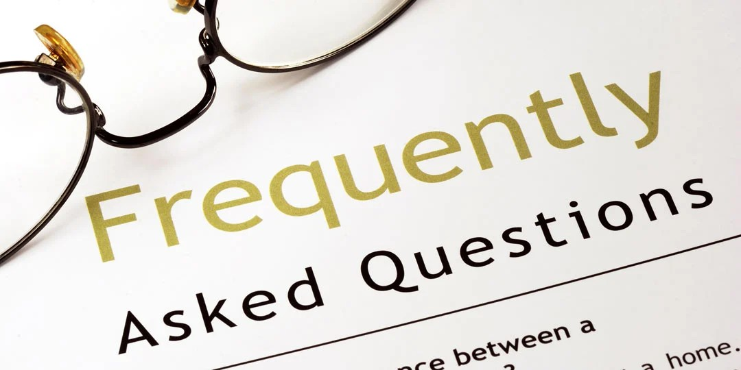 Glasses sitting on top of paper with frequently asked questions