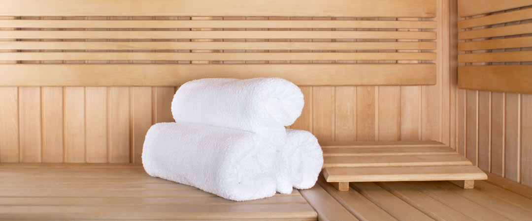Three rolled towels inside an infrared sauna