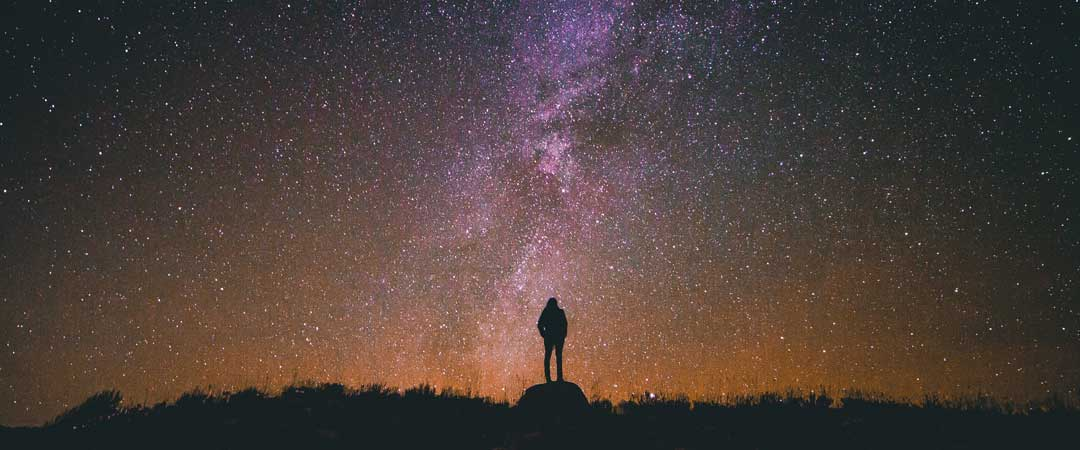 Man standing on a rock watching a sky full of stars