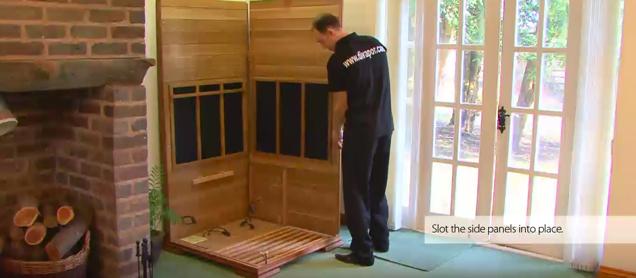 Placing side wall into base of sauna