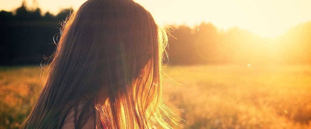 Woman looking over a field into the sun
