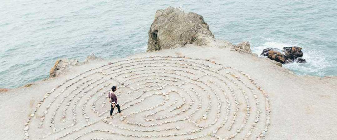 Man walking on sand along the ocean