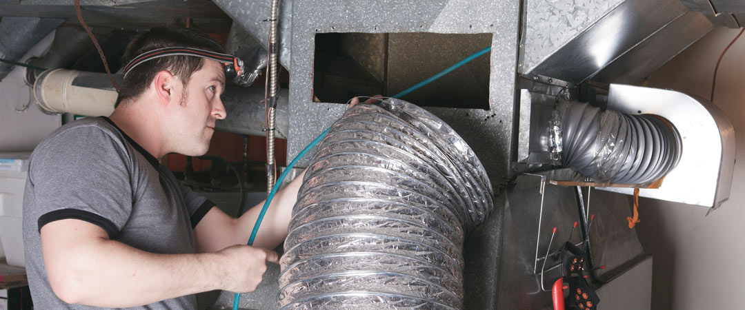 Repairman cleaning home ductwork