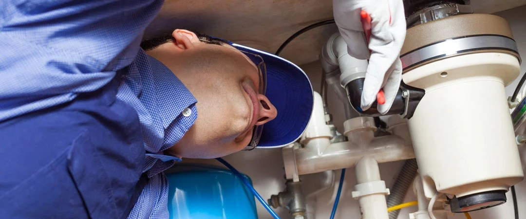 Repairman tightening clamps on garbage disposal drains