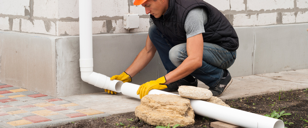 Man adding an extension to his gutter's down spout