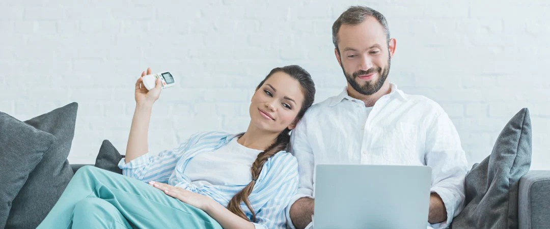 Couple sitting on a couch with sliding window air conditioner running
