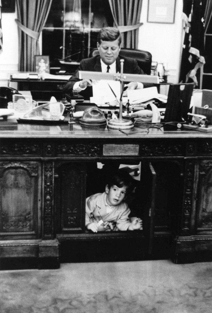 John F Kennedy seated at his desk with John Junior playing at his feet