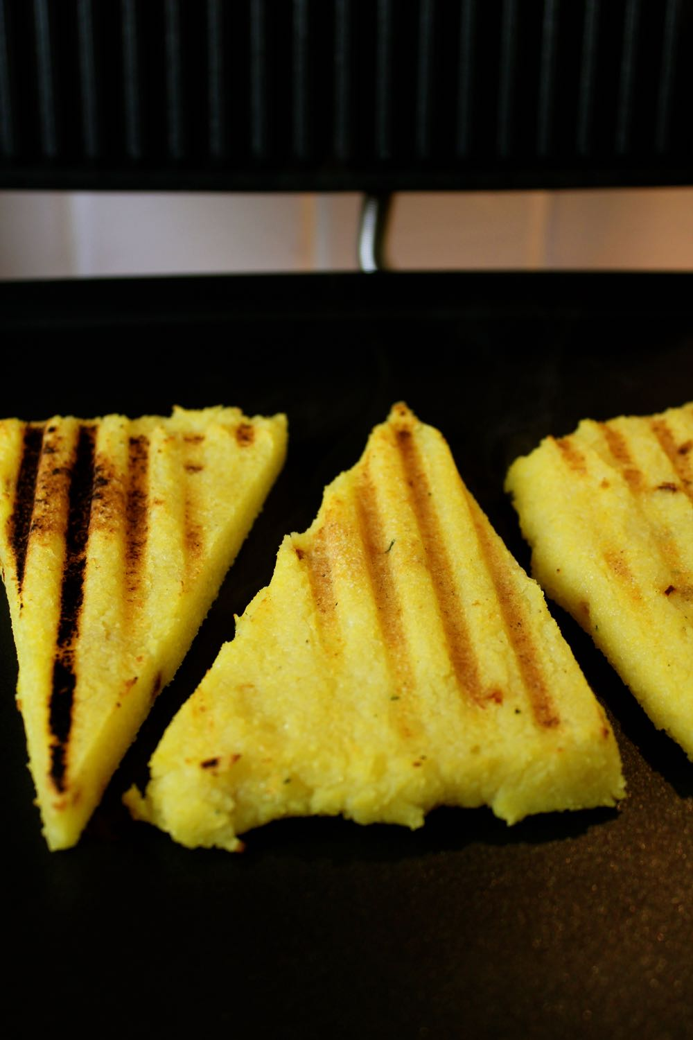 Three pieces of Griddled Polenta Bruschetta on the grill