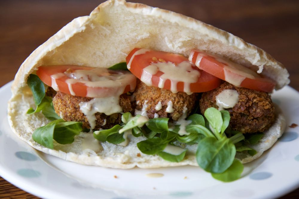 Easy Vegan Falafel - Chickpea Falafels in soft pitta pockets with crisp salad leaves, juicy tomatoes and a tahini drizzle