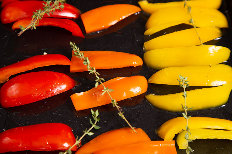 Red, orange and yellow peppers ready for roasting with thyme