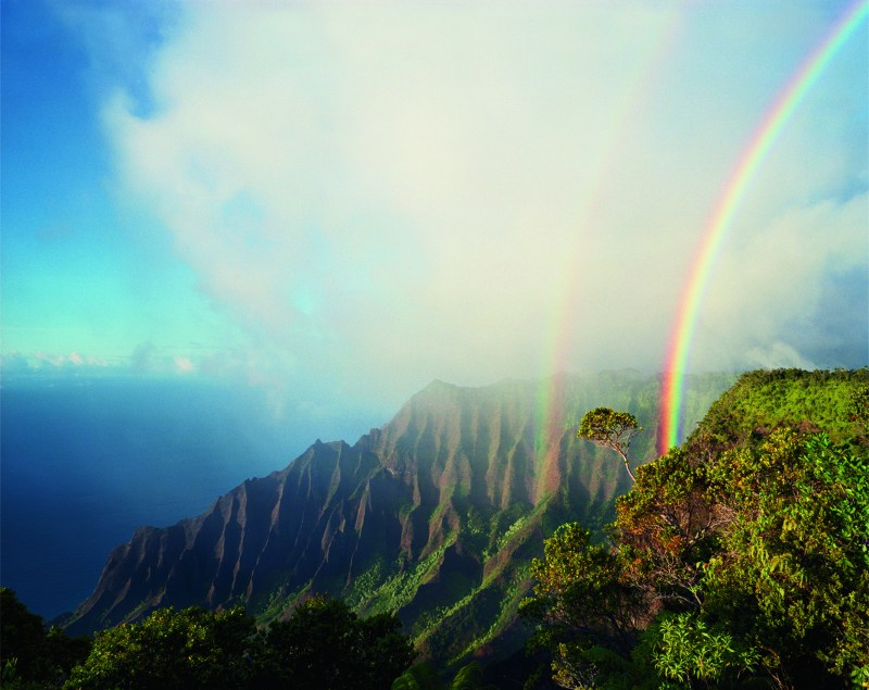 "A double rainbow arcs above the jagged cliffs and dense vegetation of Kalalau, the largest valley on Na Pali. Photo credit: Diane Cook/National Geographic ""Women of Vision"" exhibit"