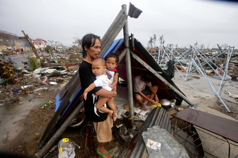 A Filipino father and his children wait for food relief outside their makeshift tent in the super typhoon devastated city of Tacloban. Photo credit: Save the Children