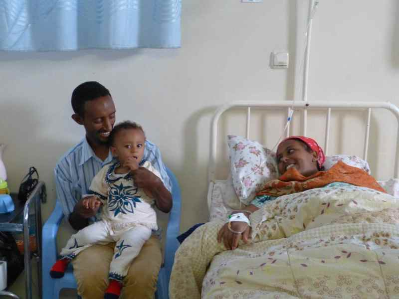 Mother who had just given birth at a hospital in Addis Ababa. Her husband and son are on the left.