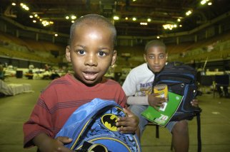 Demar Jone Hutchinson (3 yrs)with his brother 11 year-old brother Delvin in the Baton Rouge River Center. They are holding backpacks and school supplies distributed by Save the Children. Photo credit: Save the Children