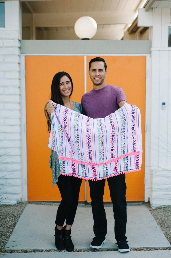 Chris and Jesenia hold up one of their blankets.