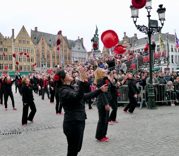 women throwing hats into the air, Bruges, Belgium