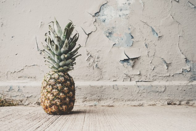Pineapple sitting on the floor in front of paint peeling wall.