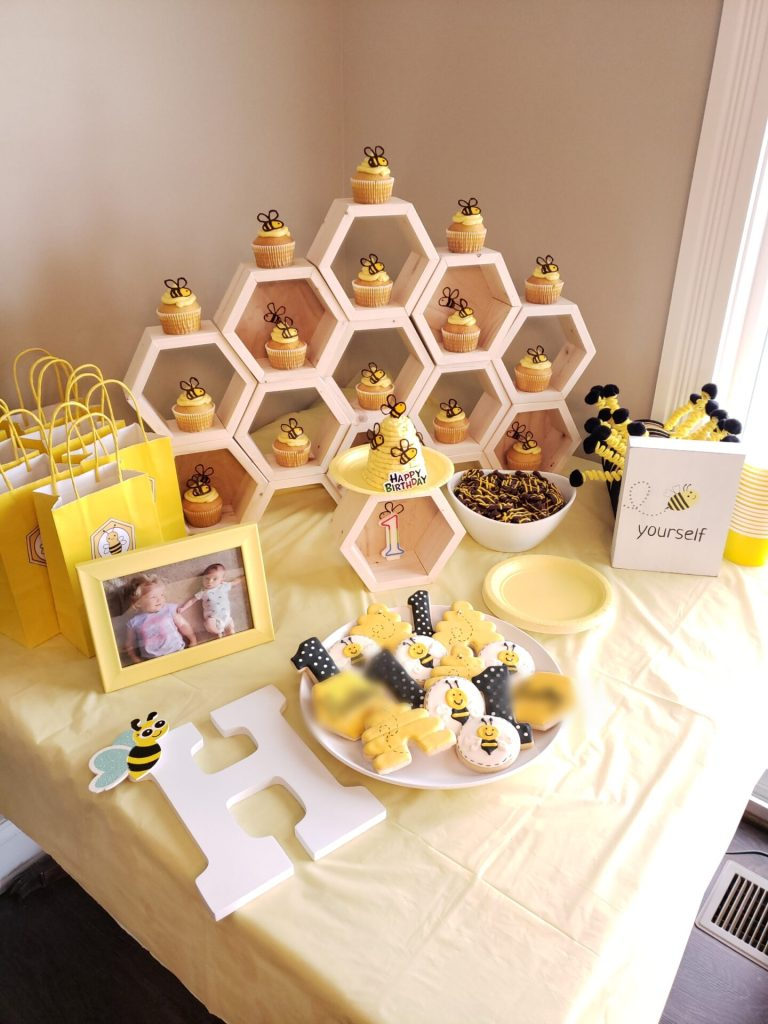 Bee-themed stacking hexagon cupcake display for a first birthday party