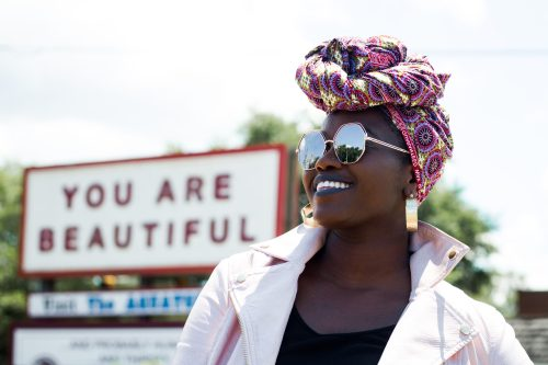 Beautiful Woman Stands Smiling by a Sign that says You Are Beautiful