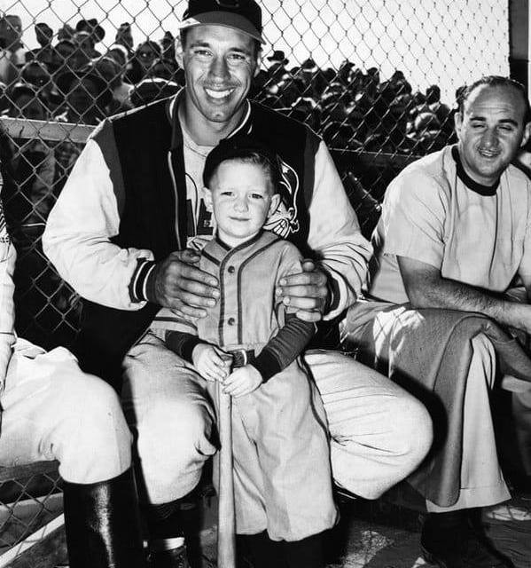 A child poses with Cleveland Indians pitcher Bob Feller at Burbank's Olive Memorial Stadium in 1949.