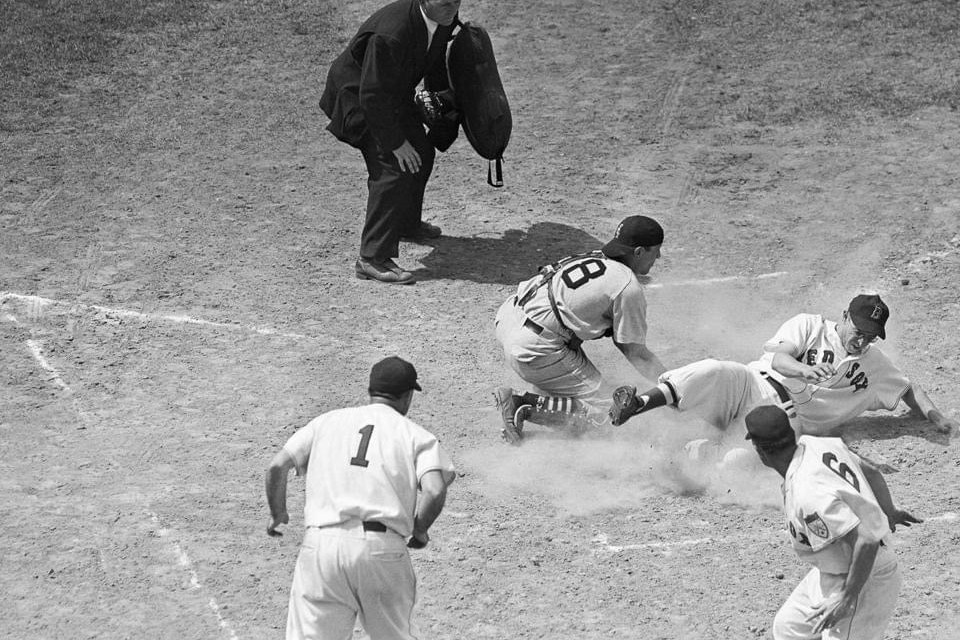 1951 Dom DiMaggio slides in safe at the plate as Bobby Doerr and Johnny Pesky look on.  White Sox catcher is Phil Masi. Ump is Ed Hurley.