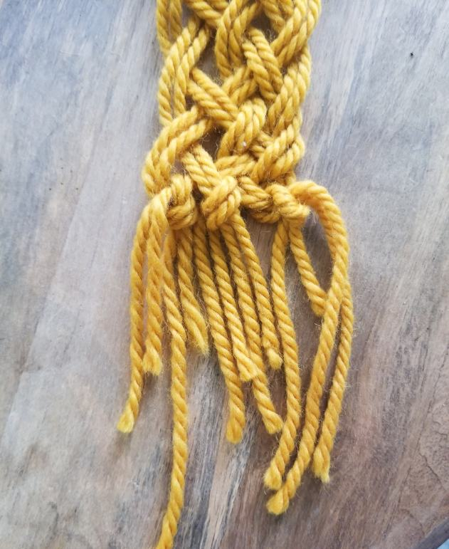 yellow marigold yellow macrame project with tied ends.
