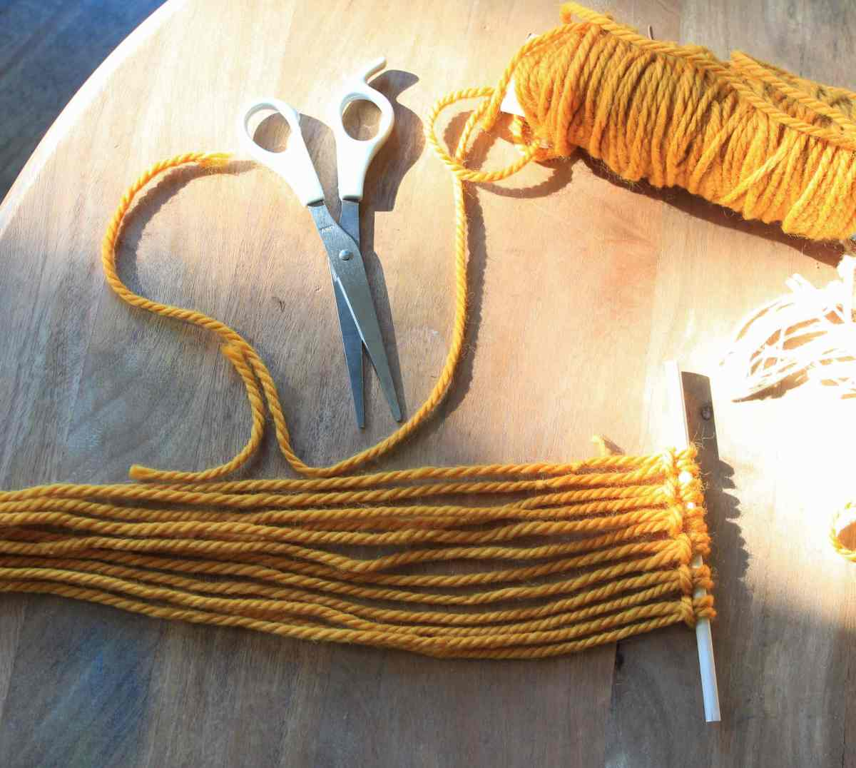 scissors next to yellow yarn and macrame project.