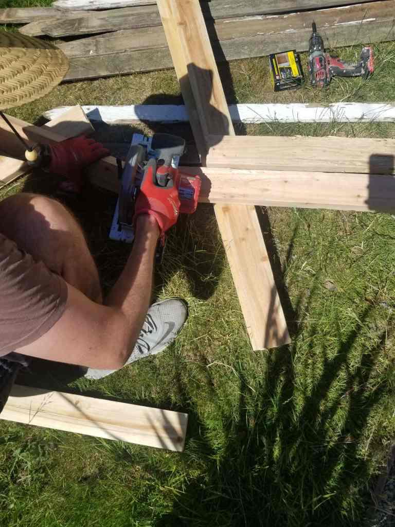 Man holding circular saw and cutting 2x4.