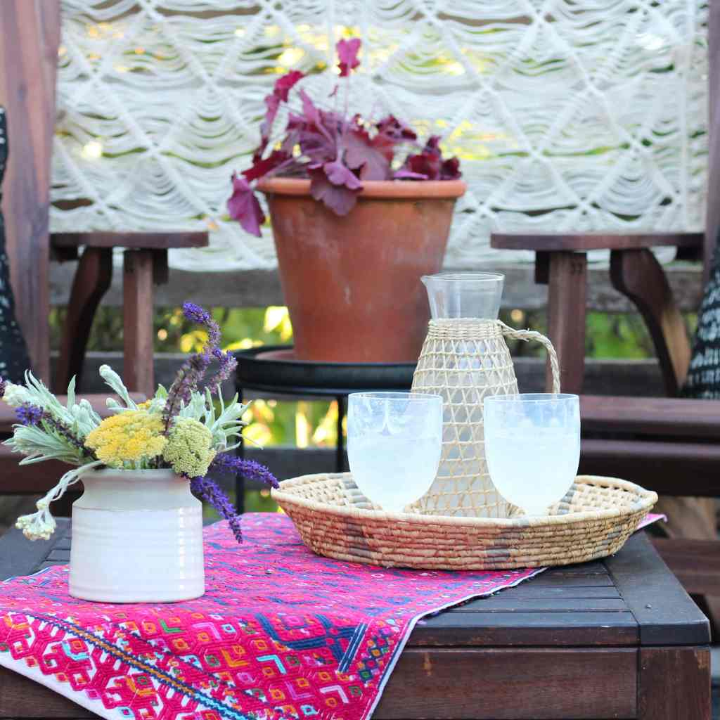 Small patio table with wildflower arrangement in vase, rattan tray and drinkware, pink embroidered table runner, and potted plants.