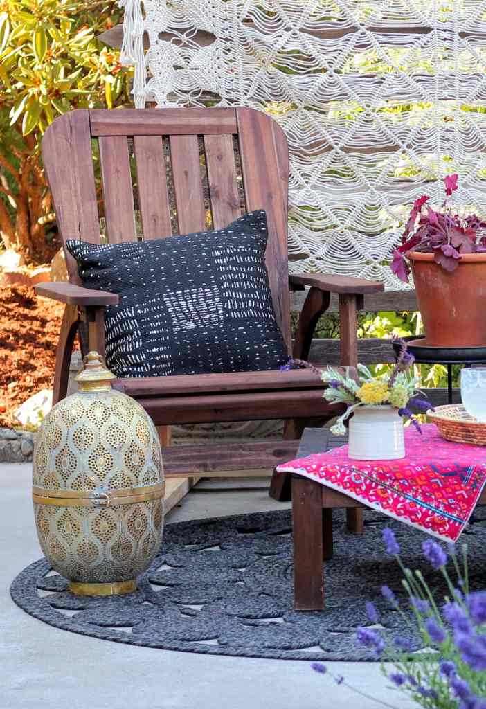 Adriondack chair with black boho pillow. Neutral macrame tapestry hanging on privacy screen. Gold lantern sitting on black rug. Flower arrangement on table.