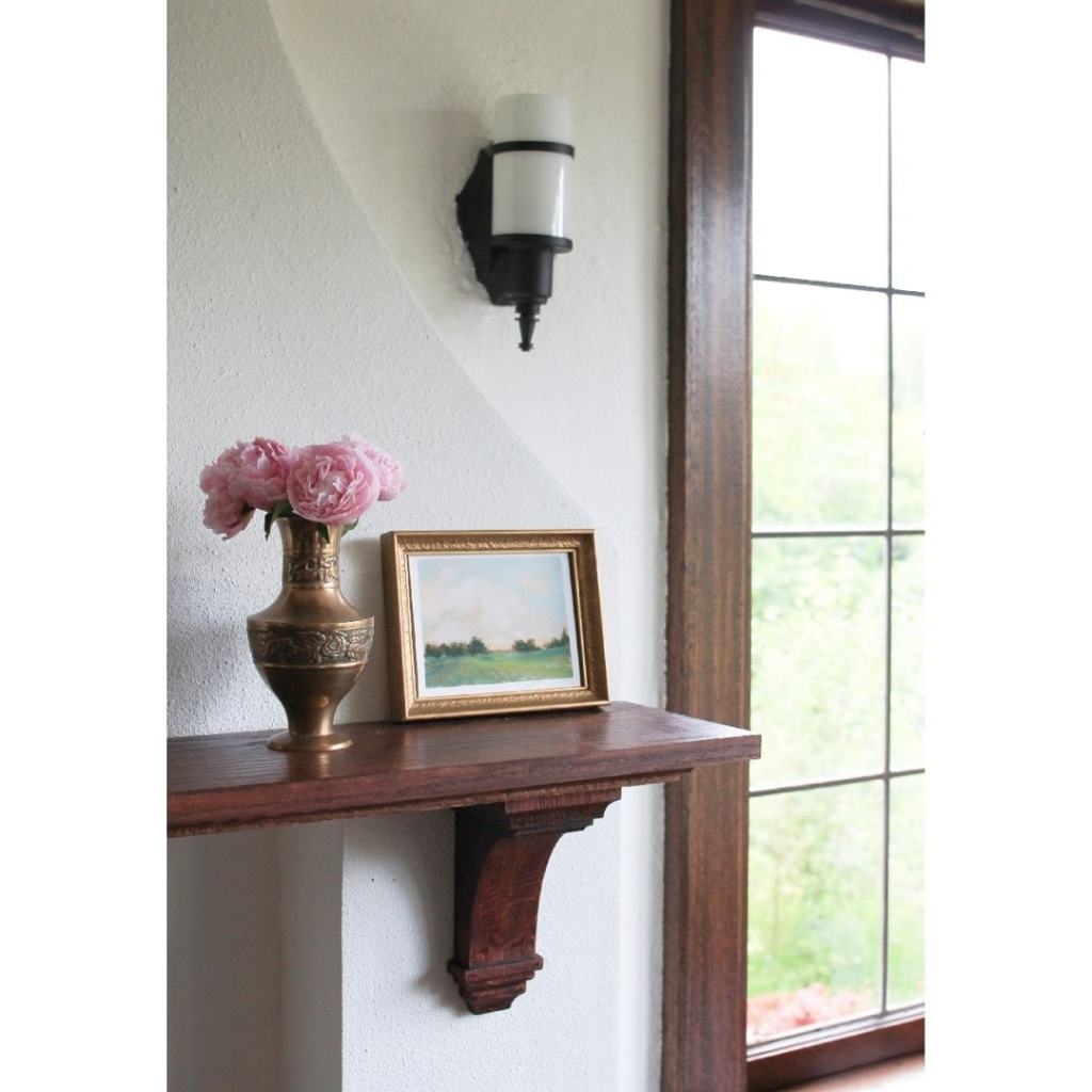 Dark wood mantle with small landscape painting and vase with flowers. Lead glass window next to mantle.