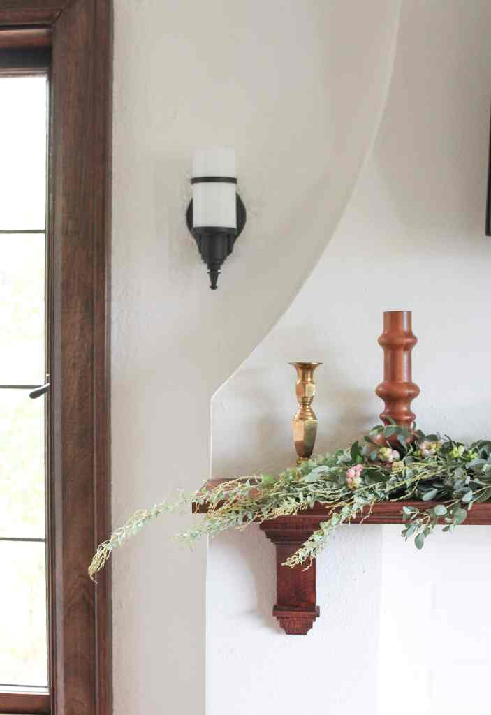 DIY wood mantle with eucalyptus garland and candlesticks.