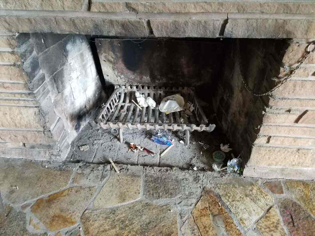 Fireplace with stone hearth and not cleaned.