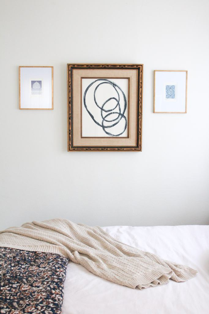 Vintage frame with abstract art hanging in the middle of two smaller gold framed pictures.