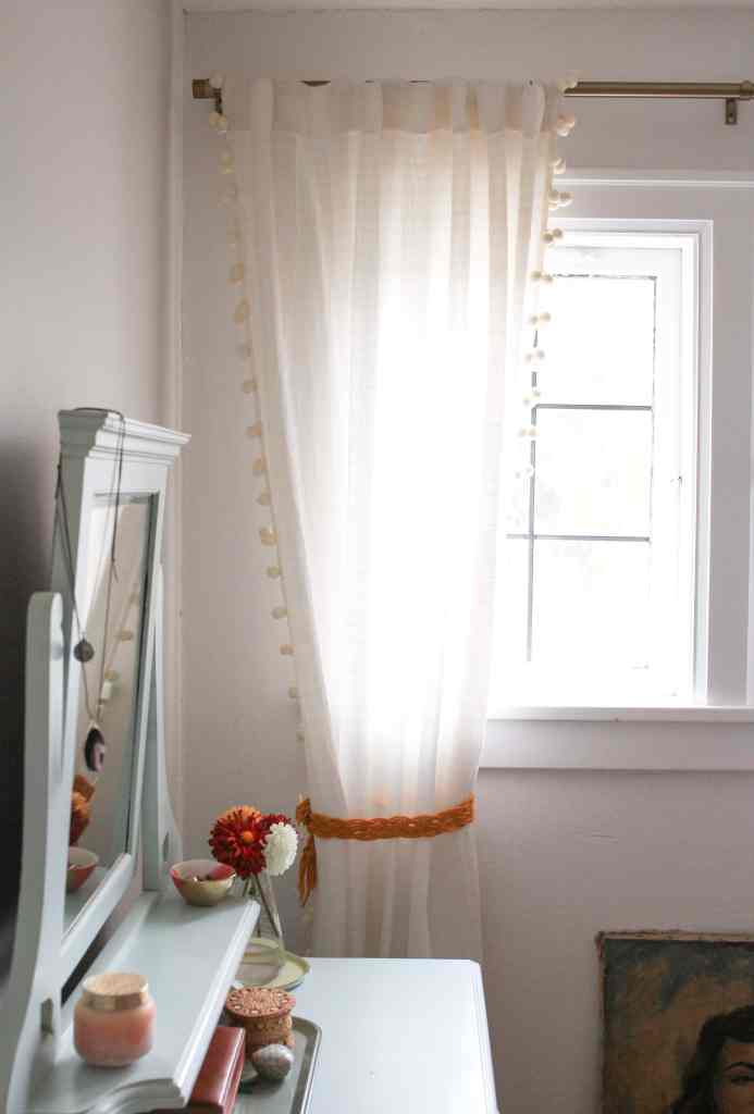 Neutral linen curtain with pom poms tied with a marigold color tie back.