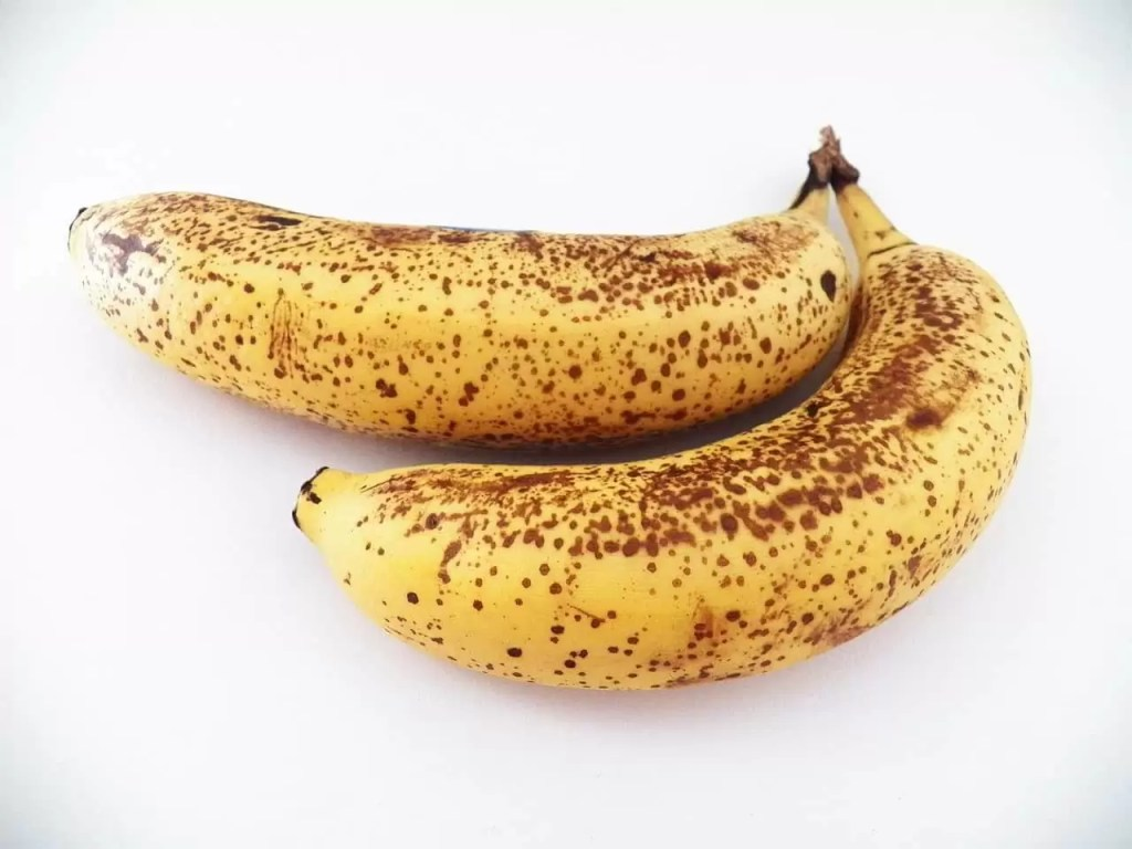 Two ripe bananas on a white surface