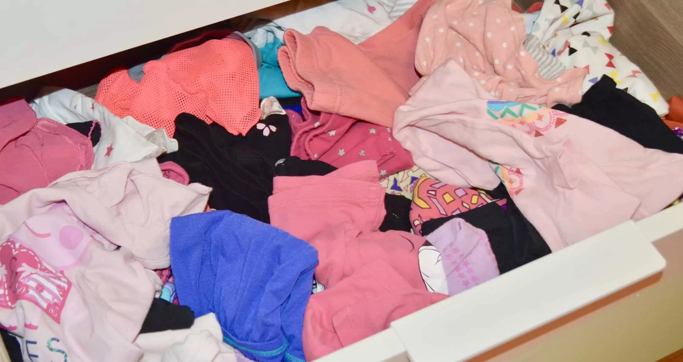 A drawer of messy unorganized girls clothes