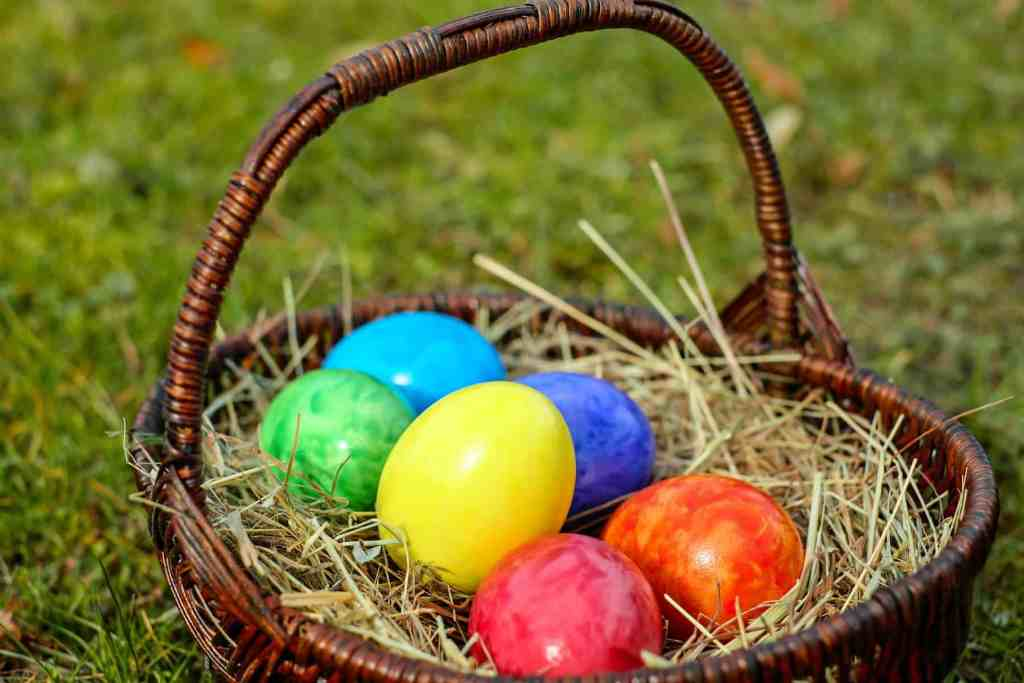 Easter basket full of colorful eggs sitting in a field