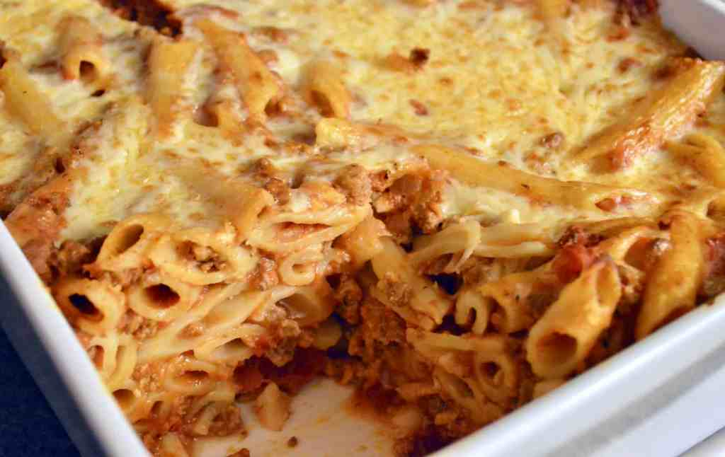 baked penne with meat sauce in a white baking dish
