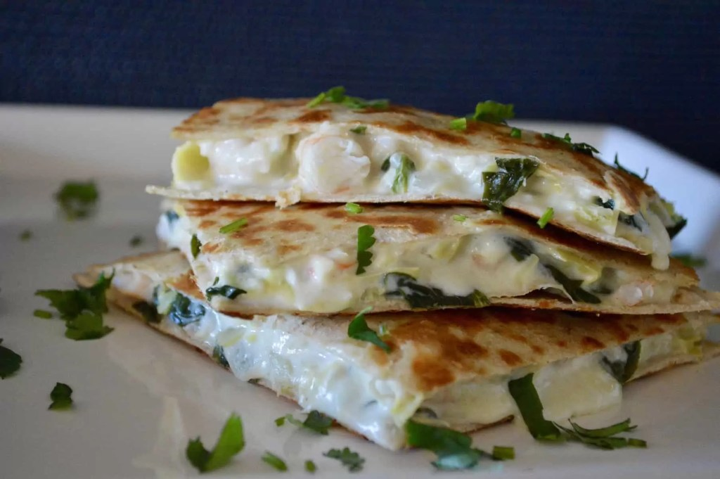 Spinach Artichoke Shrimp Quesadillas on a white plate with cilantro sprinkled