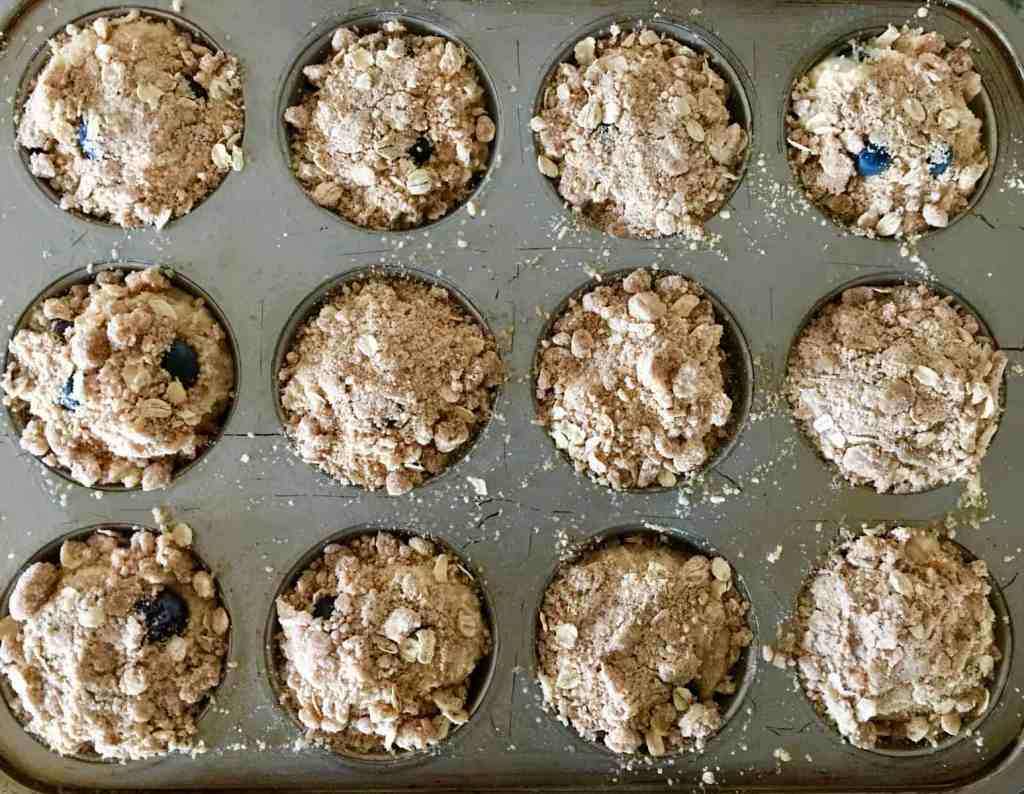 streusel topping on the blueberry muffins in the muffin tin