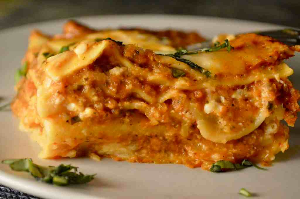 Easy Vegetable Lasagne on a white plate with chopped basil