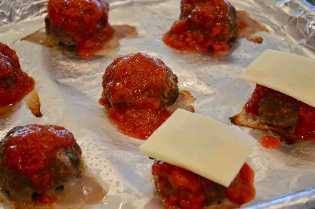 Easy Italian meatball sliders on a foil-lined baking sheet with sauce a mozzarella on top