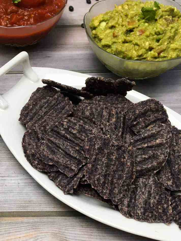 plate of black bean chips with bowl of salsa and bowl of guacamole