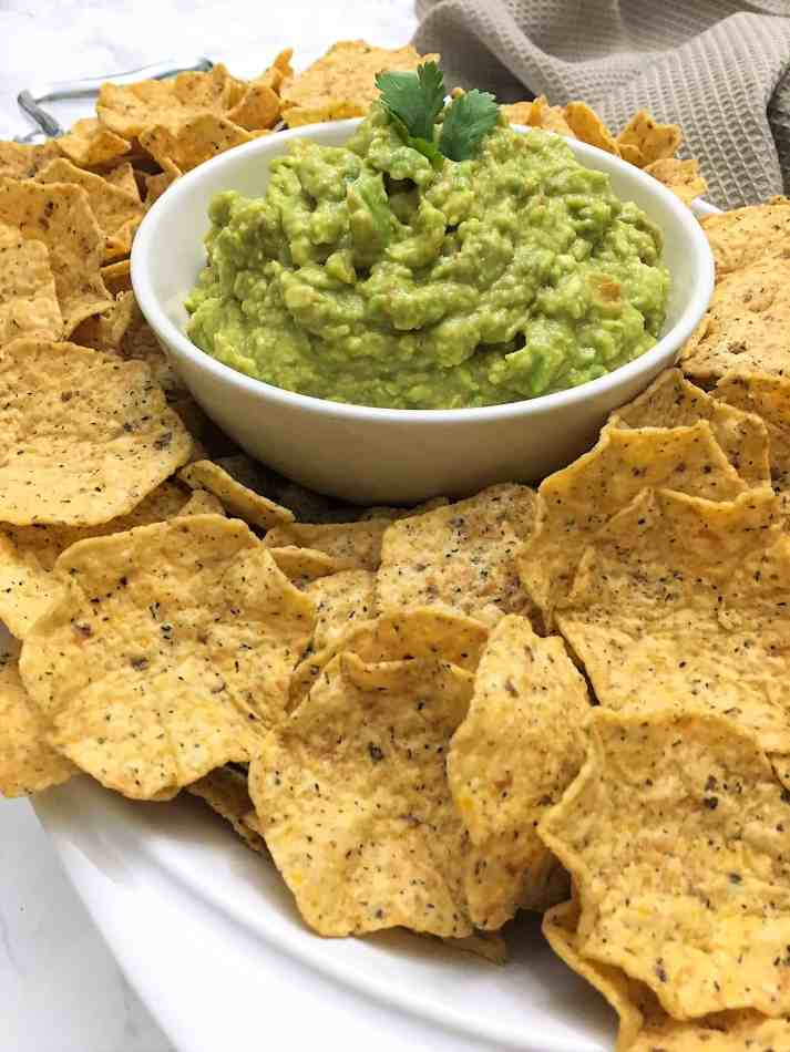 guacamole in bowl surrounded by torilla chips
