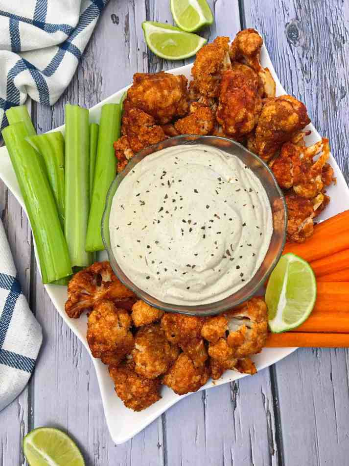 serving dish with cauliflower wings and ranch dip and celery and carrots