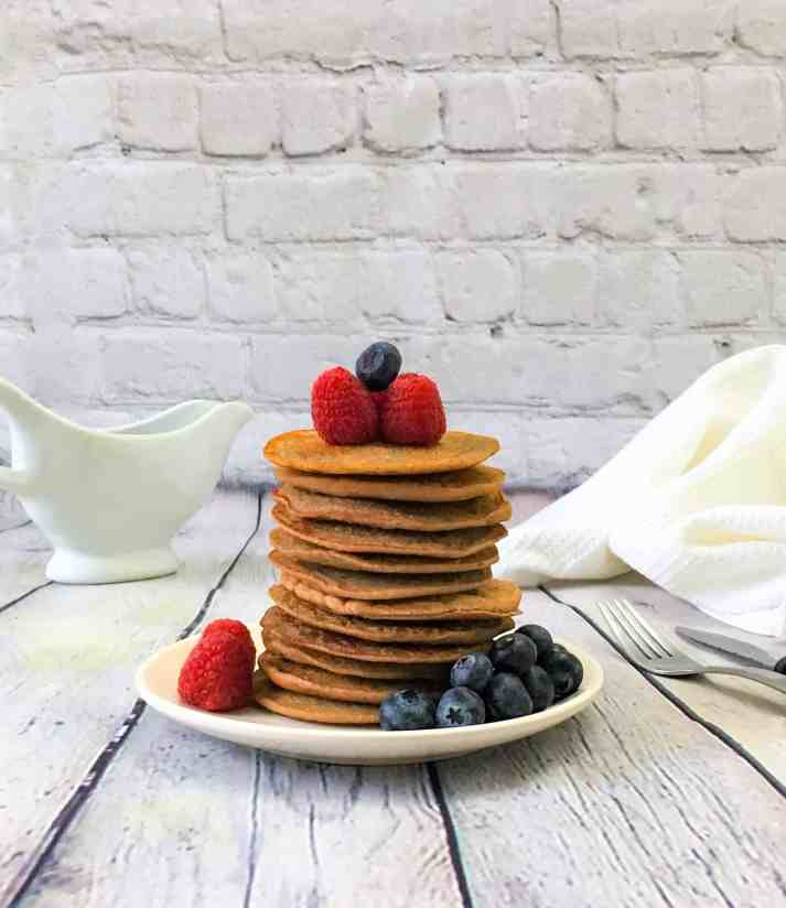 lentil banana protein pancakes stacked in plate with berries on top