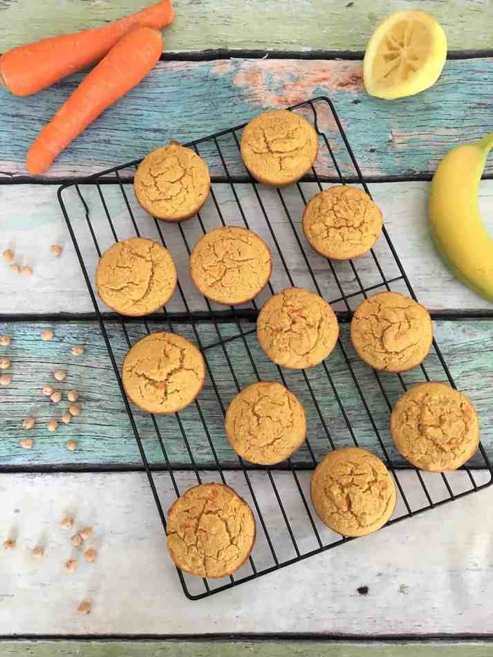 carrot cake muffins on cooling rack with carrots and banana in background