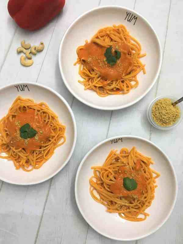 roasted red pepper pasta in three bowls garnished with vegan parmesan cheese